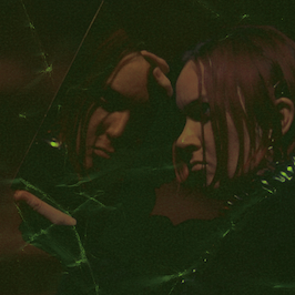 Close-up crop of art documentation, displaying a layer of crushed paper texture and eerie green light effects, applied by Mycelia Issue 3's art director, Marcus Jack. The photograph shows Michelle Hannah during a performance at Tramway for Hevi Metl (October 2019).